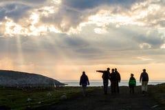 Teriberka, Russland - 30. Juli 2017: Gruppe Touristen, die auf das Ufer des Nordpolarmeers bei Sonnenuntergang gehen lizenzfreie stockfotografie