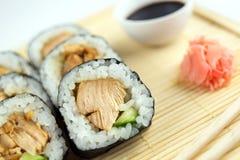 teriyaki鸡寿司卷特写镜头用黄瓜、筷子、姜和酱油 免版税库存照片
