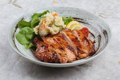 Teriyaki chicken served with potato salad, sliced lemon, totmato and green oak in round stone plate on washi Japanese paper Stock Photo