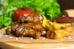 Teriyaki chicken wings and baked potato, junk food Stock Images