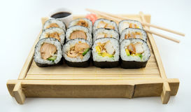 Teriyaki and fried chicken sushi rolls on Japanese bamboo mat with chopsticks, soy sauce and ginger Royalty Free Stock Photos