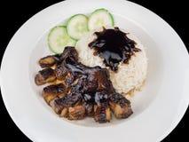 Teriyaki grillé de poulet avec du riz et des légumes d'un plat blanc d'isolement sur le fond noir avec le chemin de coupure Image stock