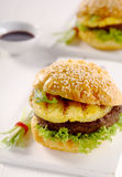 Teriyaki Pineapple burger on a sesame bun. With a grilled pineapple ring and beef patty on fresh lettuce served on a plate in a steakhouse Stock Photos