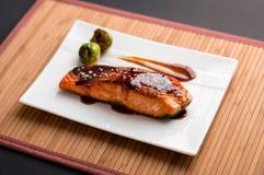 Teriyaki salmon plate on bamboo mat. Stock Images
