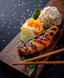 Teriyaki salmon with rice on a wooden platter Stock Image