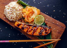 Teriyaki salmon with rice on a wooden platter Stock Photos