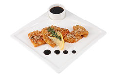 Teriyaki sauce calamary on square serving dish, isolated on whit. Teriyaki squid with lemon, sesame seeds and sprig rosemary on a white square serving plate Stock Photography