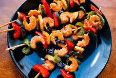 Teriyaki shrimps with zucchini and red pepper on plate. Teriyaki shrimps with zucchini and red pepper on black plate, slightly toned Royalty Free Stock Images