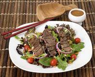 Teriyaki Steak Salad. On Fresh Greens with Chopsticks and Thai Peanut Dressing Royalty Free Stock Image