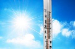 Termómetro contra la perspectiva de un resplandor caliente azul de las nubes y del sol, concepto de tiempo caliente Sobre 40 grad imagenes de archivo