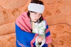 Termómetro de la muchacha en el sofá Imagen de archivo