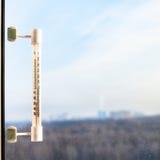Termómetro en el cristal de ventana en día de invierno frío Foto de archivo libre de regalías