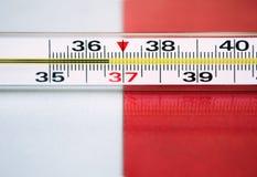 Termómetro en un fondo blanco-rojo Imagen de archivo libre de regalías