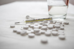 Termómetro médico y en las píldoras de la tabla y el vidrio blancos de agua Fotos de archivo