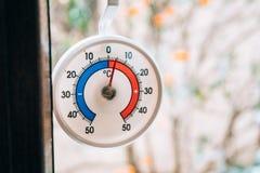 Termómetro redondo en la ventana 5 grados de cent3igrado La nieve hacia fuera Imágenes de archivo libres de regalías