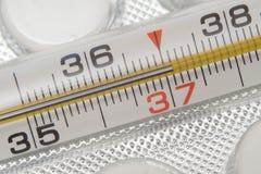 Termómetro y píldoras médicos en el fondo blanco Medicinas y termómetro médico fotos de archivo libres de regalías