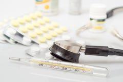 Termómetro y píldoras médicos en el fondo blanco Medicinas y termómetro médico fotografía de archivo