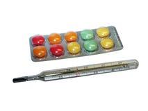Termómetro y vitaminas Fotos de archivo libres de regalías
