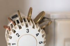 Termóstato del radiador con las monedas euro Ahorre los costes de la calefacción reduciendo el consumo del gas Foto de archivo