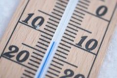 Termômetro de madeira na neve com macro da temperatura de congelação imagens de stock