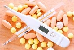 Termômetro e comprimidos Fotos de Stock