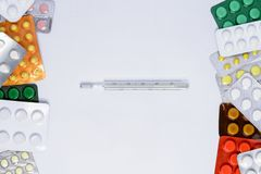 Termômetro em um fundo branco entre comprimidos de cores diferentes nos pacotes imagens de stock