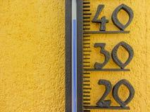 Termômetro na parede amarela que mede a temperatura do ar externo sobre quarenta graus Célsio Foto de Stock