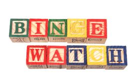 The term binge watching visually displayed on a white background. The term binge watching visually displayed using colorful wooden toy blocks on a white Royalty Free Stock Photos