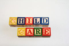 The term child care. Displayed visually using colorful wooden blocks on a white background in landscape format Stock Image
