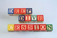 The term deep dive cession visually displayed. On a white background using colorful wooden toy blocks in landscape format with copy space Royalty Free Stock Photo