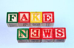 The term fake news spelled wrong. The term fake news but spelled wrong displayed visually on a clear background using colorful wooden toy blocks in landscape Stock Photography
