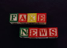 The term fake news. Visually displayed using colorful wooden toy blocks on a black background in landscape format Royalty Free Stock Images