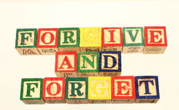 The term forgive and forget. Displayed visually on a white background using colorful wooden toy blocks Royalty Free Stock Images