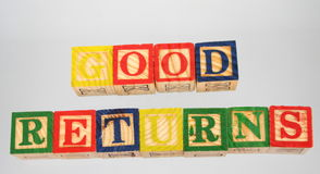 The term good returns presented visually. The phrase good returns displayed visually on a white background using colorful wooden blocks Stock Images