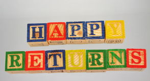 The term happy returns presented visually. The phrase happy returns displayed visually on a white background using colorful wooden blocks Royalty Free Stock Photo