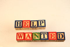 The term help wanted. Visually displayed using colorful wooden blocks Royalty Free Stock Photo