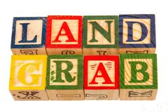 The term land grab visually displayed. On a white background using colorful wooden toy blocks image in landscape format with copy space Stock Image