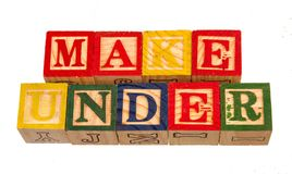The term make under visually displayed. On a white background using colorful wooden toy blocks image in landscape format with copy space Stock Image