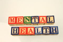 The term mental health. Displayed visually on a white background using colorful wooden toy blocks Stock Photos
