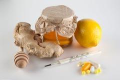 Termômetro, comprimidos e vitaminas CONTRA o frasco do mel, gengibre, limão Fotografia de Stock Royalty Free
