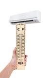 Termômetro de madeira à disposição na parte dianteira do condicionador de ar Isolador Imagem de Stock