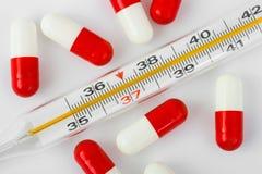 Termômetro e comprimidos Imagens de Stock