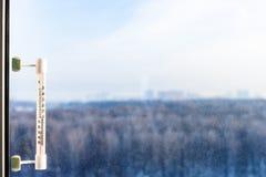Termômetro no vidro de janela no dia de inverno frio Fotos de Stock Royalty Free