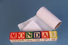 The term Monday and a roll of toilet paper visually displayed. On a white background using colorful wooden toy blocks in landscape format with copy space Stock Photography