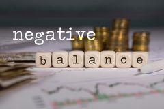 Term NEGATIVE BALANCE composed of wooden letters. Stacks of coins in the background. Closeup stock photography