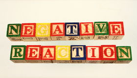 The term negative reaction. Displayed visually on a white background using colorful wooden toy blocks Stock Photo