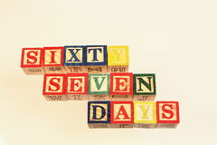 The term sixty seven days displayed visually. Using colorful wooden blocks on a white background in landscape format with copy space Royalty Free Stock Images