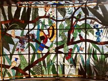A beautiful stained glass window with many colorful birds and animals. The term stained glass can refer to coloured glass as a material or to works created from stock images