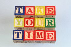 The term take your time visually displayed. On a white background using colorful wooden toy blocks in landscape format with copy space Stock Photos