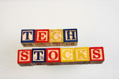 The term tech stocks. Displayed visually using colorful wooden blocks on a white background in landscape format Royalty Free Stock Photo